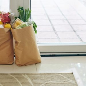Healthy food in paper bags at entrance door of house, contract free delivery concept